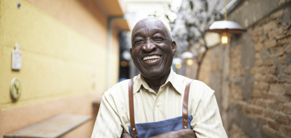 Laughing senior man of colour wearing an apron