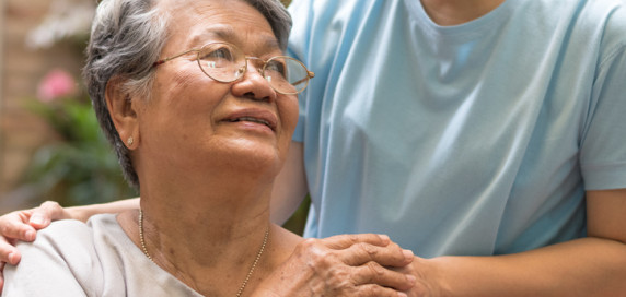 Older Asian woman sitting with a caregiver's hand on her shoulder