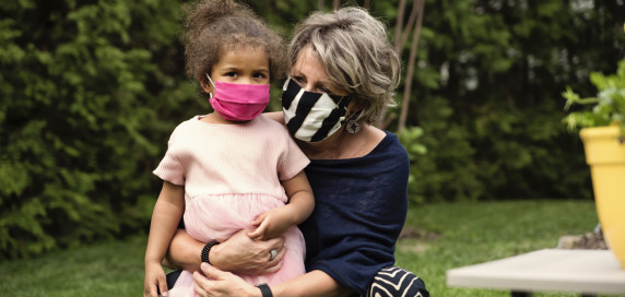 Older woman huging child wearing masks