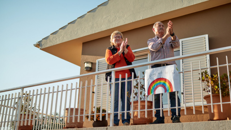 Senior couple clapping from their balcony