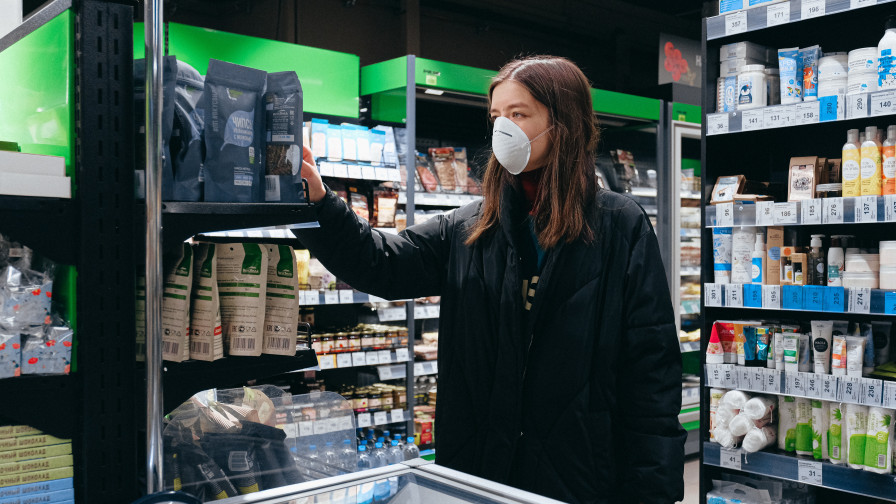 Woman in mask shopping at supermarket