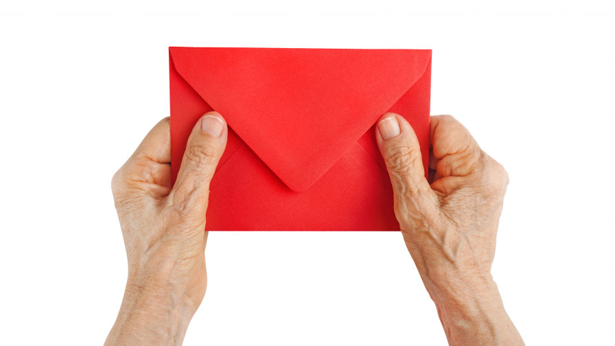 Older person holding a red envelope